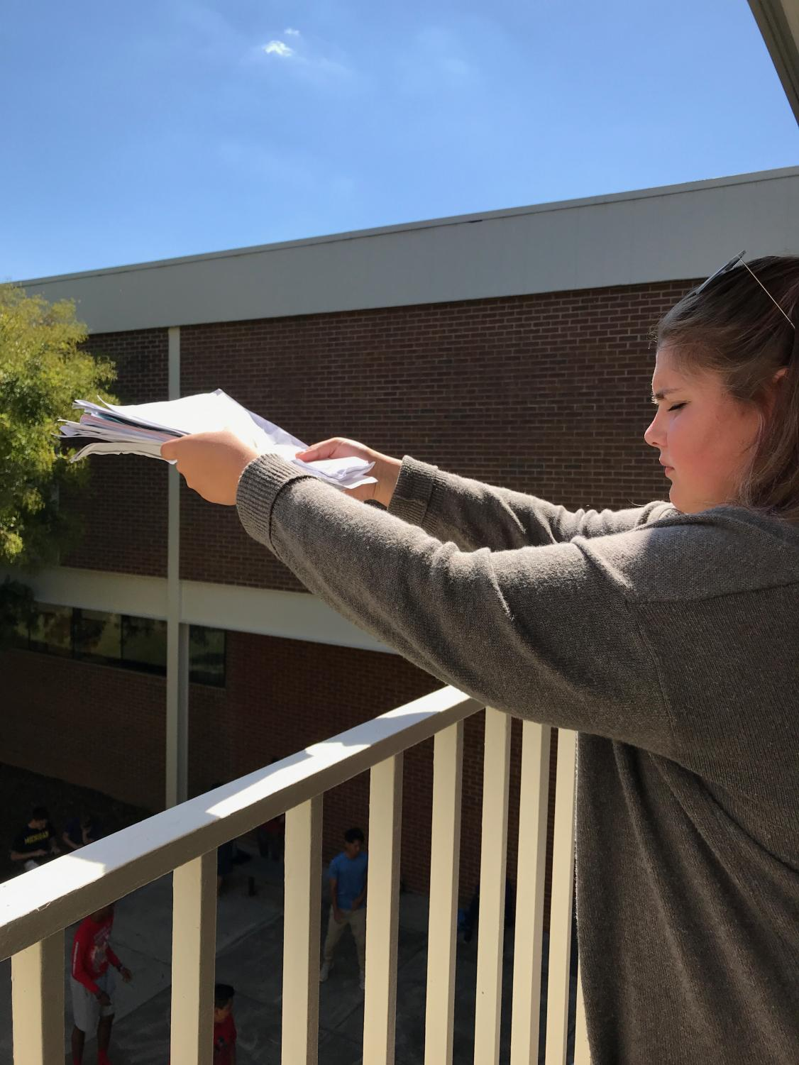 Gabby Safley (12) prepares to throw a stack of cornell notes off the balcony.