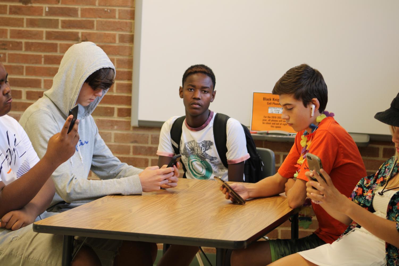 Freshman students, Santino Green, Malachi Banks, and Asher Friedman on phones during class. Accompanied by sophomores Jadie Bastiaan Beatley and Sebastian Krebs.