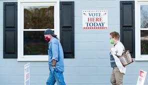 Voters wait in line to cast their ballots on Election Day, 2020